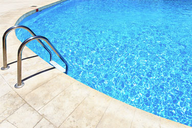 A ladder leading into a pool with clear blue water.